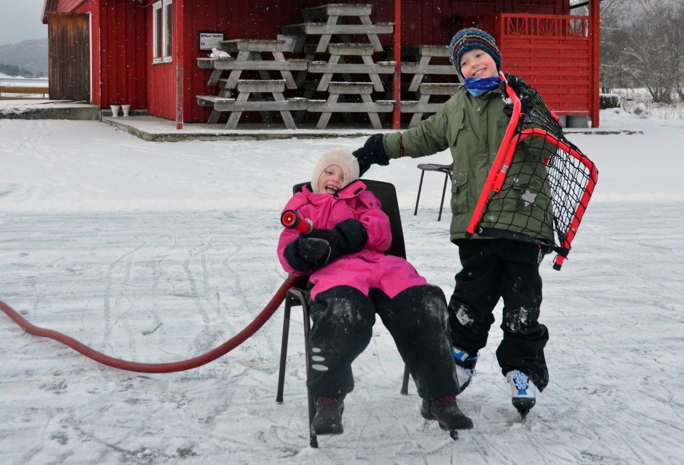 Maria og Ingebrigt er klare med vannslangen for å lage is på Bordholmen.  Foto: Jon Olav Ørsal