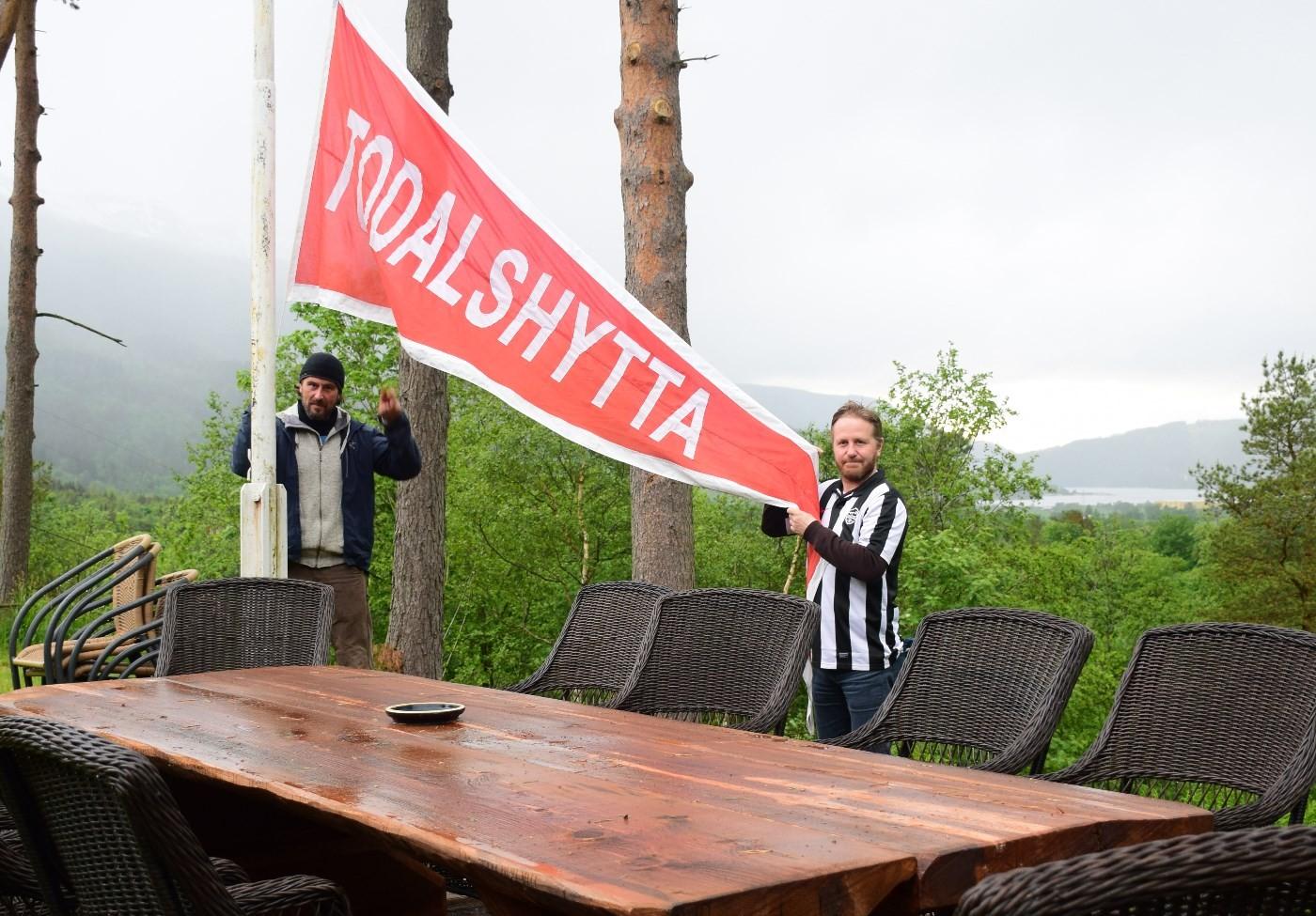 Todalshytta opna for sesongen i dag - her får Eric Malling hjelp frå Knut Bergli til å heise vimpelen og markere at ny sesong er i gang.  Foto: Jon Olav Ørsal