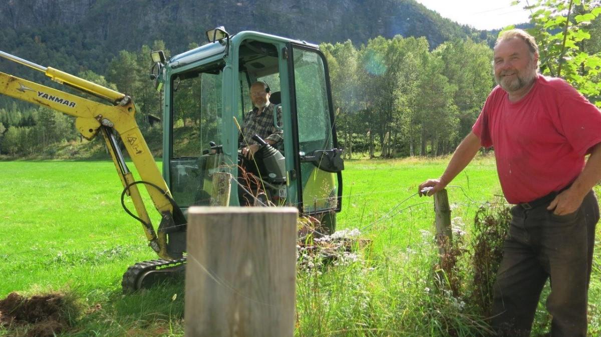 Sigfred Gravvold i gravemaskina og Jon Reidar Husby ved utgardspålen, blide arbeidskarar i finveret!