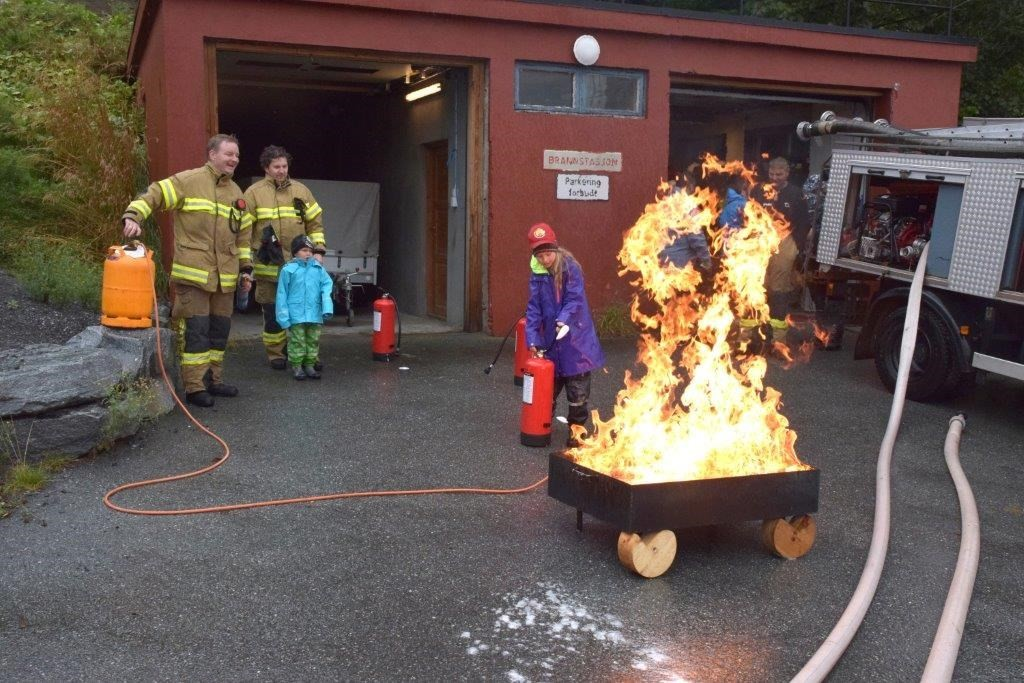 Både store og små fikk prøve å sløkke brann under brannverndagen på Kvanne. Otto Kvande og Per Egil Fiske påasser på at alt foregår i trygge former.  Foto: Jon Olav Ørsal