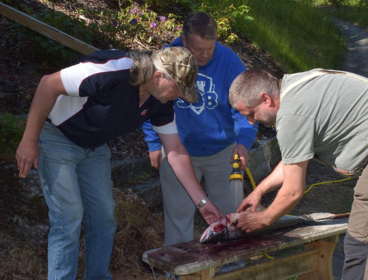 Her slaktes laksen til Frank Haugrim - den blir fredagsmiddag på Todalshytta. Frå venstre Ivar Borthen, Roar Lindbeck og Frank Hauggrim.  Foto: Jon Olav Ørsal