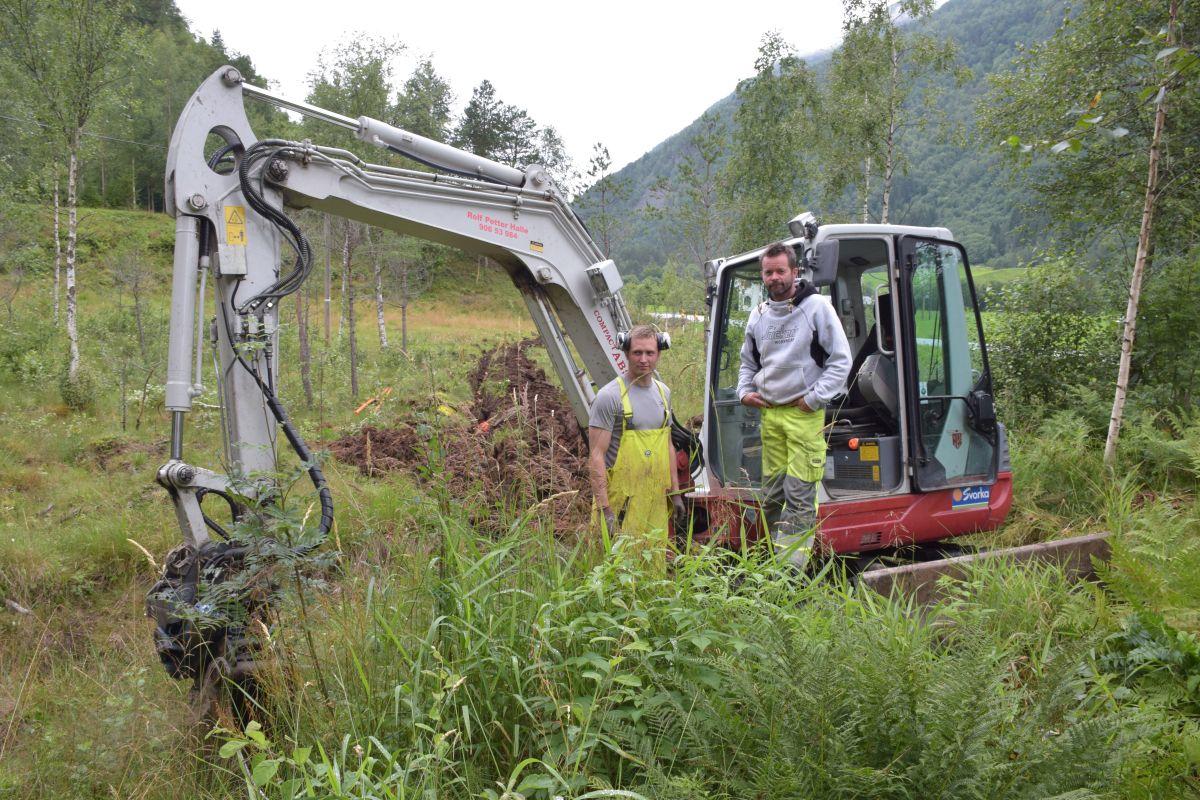 Grov ned rør for fiberbreiband i Brusetmarka i sommar. Joar Inge Gjeldnes og Rolf Petter Halle. Arkivfoto: Jon Olav Øsal