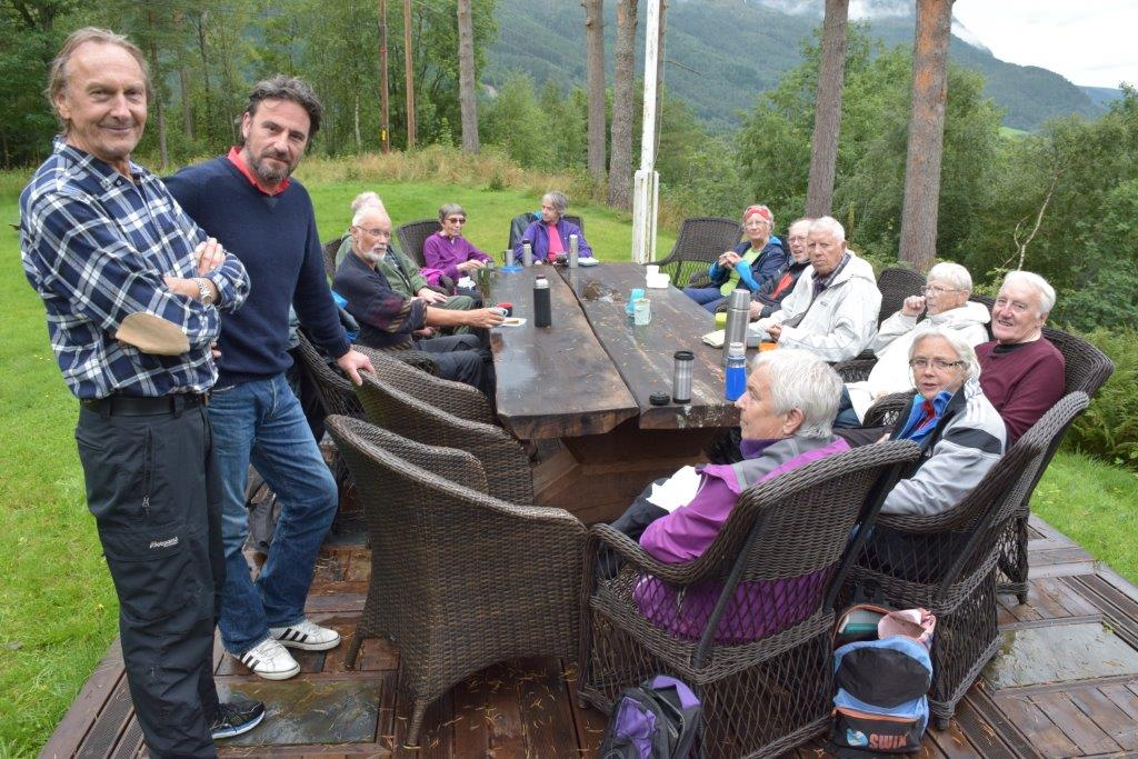 Samling rundt langbordet på Todalshytta - ståande liar Kristian Ranes og Eric Malling som er vert på Todalshytta.   Foto: Jon Olav Ørsal