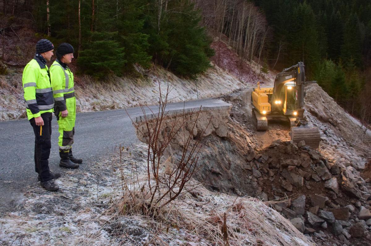 Alf Magne Sande og Gunnar Bøe frå Surnadal kommune følgjer arbeidet med gravemaskina til Per Gjeldnes.  Foto: Jon Olav Ørsal