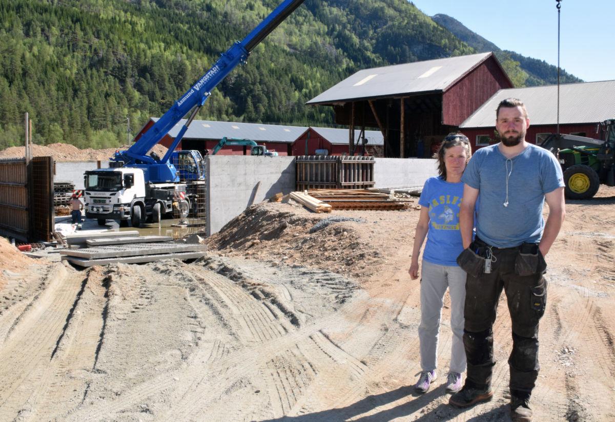 Olaug og sonen Aasmund framfor det nye fjøsbygget som er under oppføring.  Foto: Jon Olav Ørsal