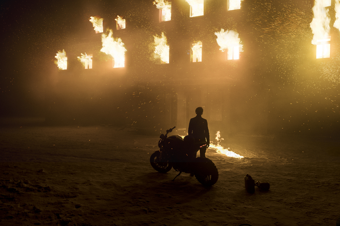 Lisbeth Salander (Claire Foy) with her bike outside burning Brandmauer manor in Columbia Pictures' THE GIRL IN THE SPIDER'S WEB.