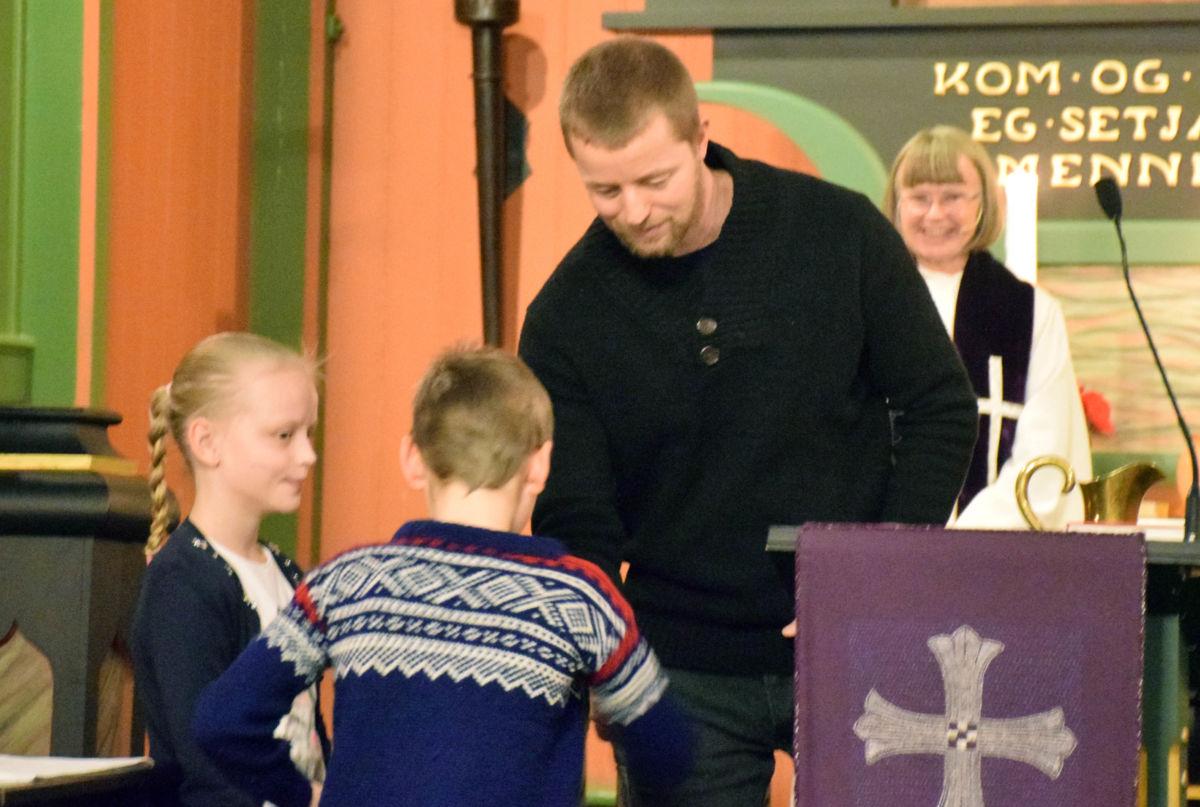 Maria K. Bergli og Tor Asbjørn M. Karlsen får kvar sin bibel med Anders Gjeldnes frå soknerådet.  Foto: Jon Olav Ørsal