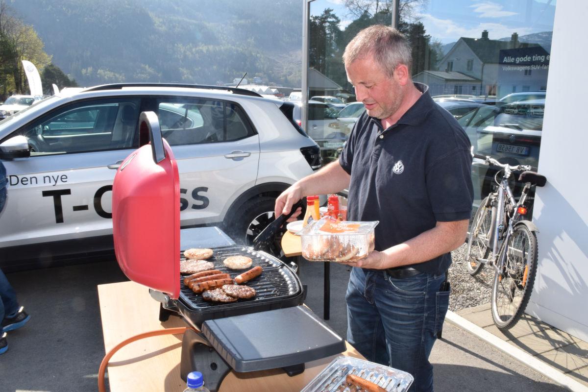 Lars Kristian Todal hos Sveen Auto hadde fyrt opp grillen og frista kundane med grillmat.  Foto: Jon Olav Ørsal