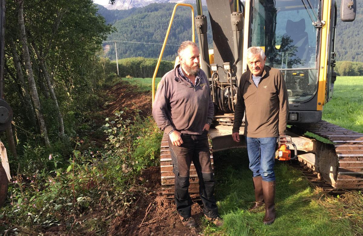 Anleggsarbeidet er i gang - Per Gjeldnes med gravemaskin og Ragnar Halle med motorsag.  Foto: Jon Olav Ørsal