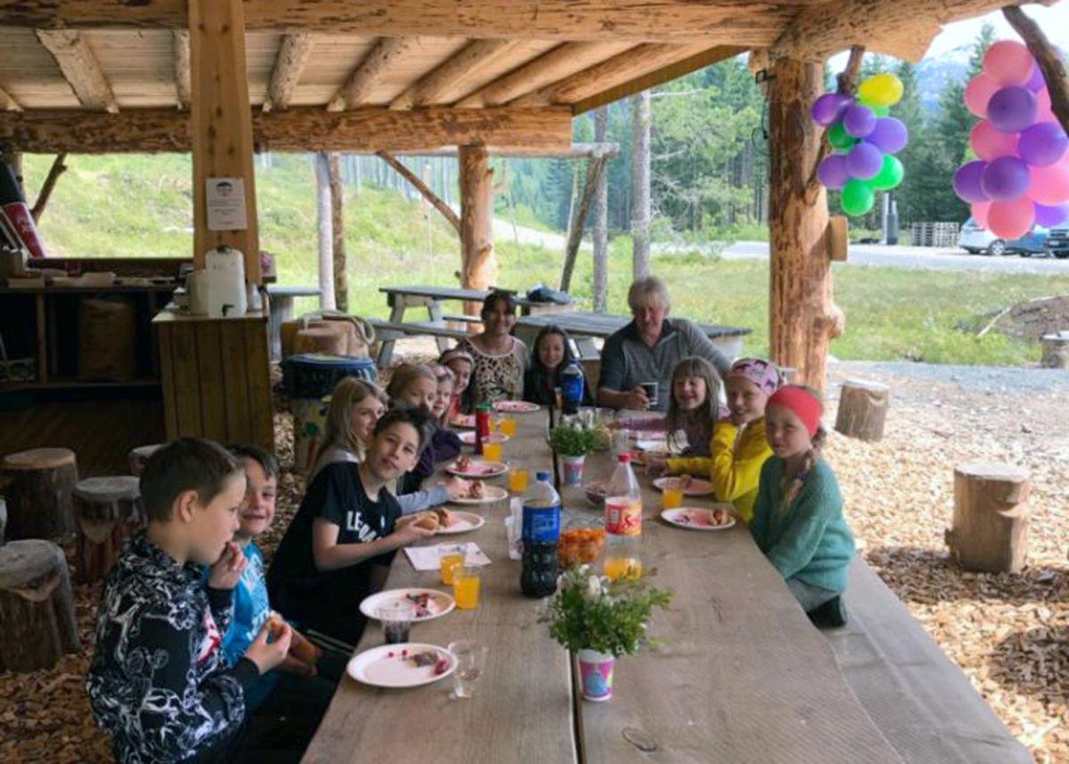 Bursdagsfeiring rundt langbordet i gapahuken på Tjønnmyran.  Foto JN