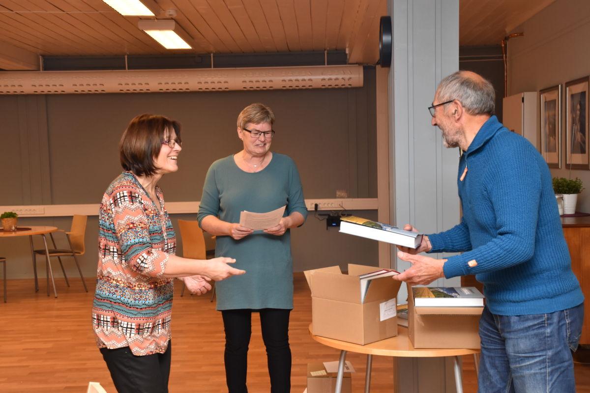Dei to redaktørane - Norunn Holten og Siv Snekvik belønna medhjelparane med eit eksemplar av bygdeboka - her er det Oddvar kvand som får sitt eksemplar.  Foto: Jon Olav Ørsal