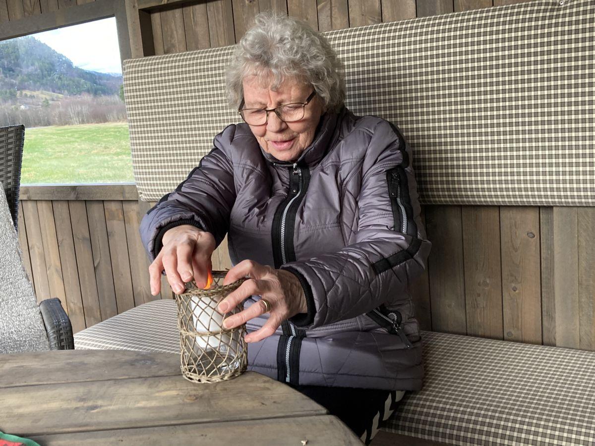 Liv Larsen skaifta batteri i den lille lykta som står på bordet i gapahuken og gir god julestemning.  Foto: Jon Olav Ørsal
